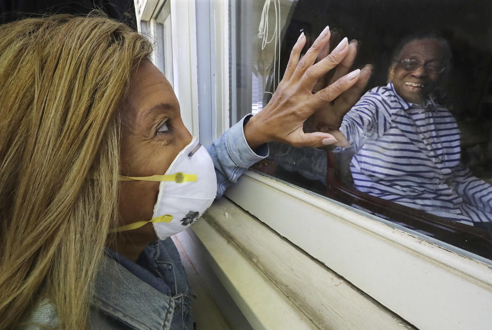 """Camilla White visits her mother Lillian Barber, 90, from outside, seeing her through the window while touching fingertips through the glass at Cottage Landing Assisted Living on Tuesday, April 28, 2020, in Carrollton, Ga. White didn't discover there had been several deaths at the home from coronavirus and a significant outbreak until seeing the info on a state website and said that before the outbreak """"I would go inside and just lay my head in her lap, but I can't do none of that anymore."""" (Curtis Compton/Atlanta Journal-Constitution via AP)"""