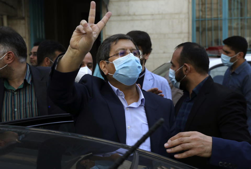 Candidate for the presidential election Abdolnasser Hemmati, former Central Bank chief, flashes the victory sign after voting at a polling station Tehran, Iran, Friday, June 18, 2021. Iran began voting Friday in a presidential election tipped in the favor of a hard-line protege of Supreme Leader Ayatollah Ali Khamenei, fueling public apathy and sparking calls for a boycott in the Islamic Republic. (AP Photo/Vahid Salemi)
