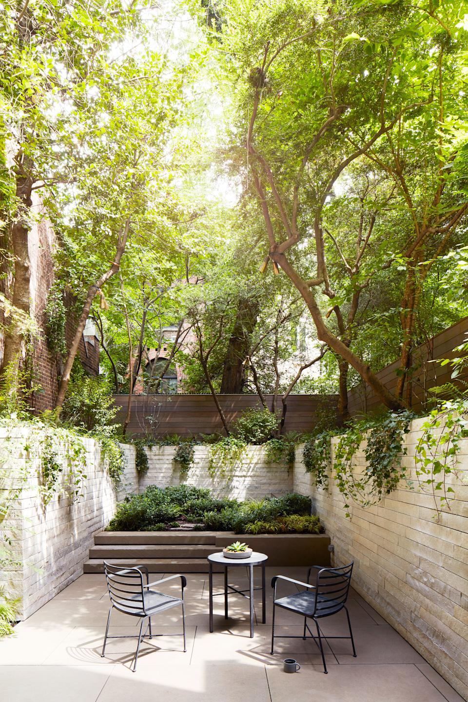 The rear garden features limestone retaining walls and flooring. Table and chairs by Munder Skiles.