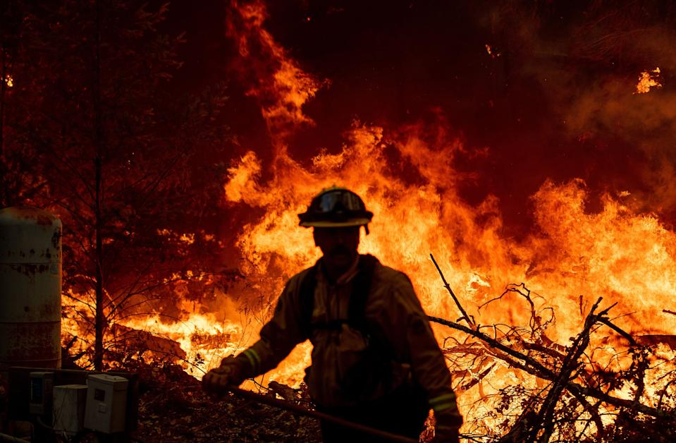 A Marin County firefighter helps to build containment lines during the Glass fire in St. Helena, Calif. on Sept. 27, 2020.
