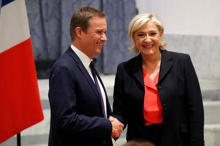 Marine Le Pen (R) French National Front (FN) political party leader and candidate for French 2017 presidential election shakes hands with Debout La France group former candidate Nicolas Dupont-Aignan after a news conference in Paris, France, April 29, 2017. REUTERS/Charles Platiau