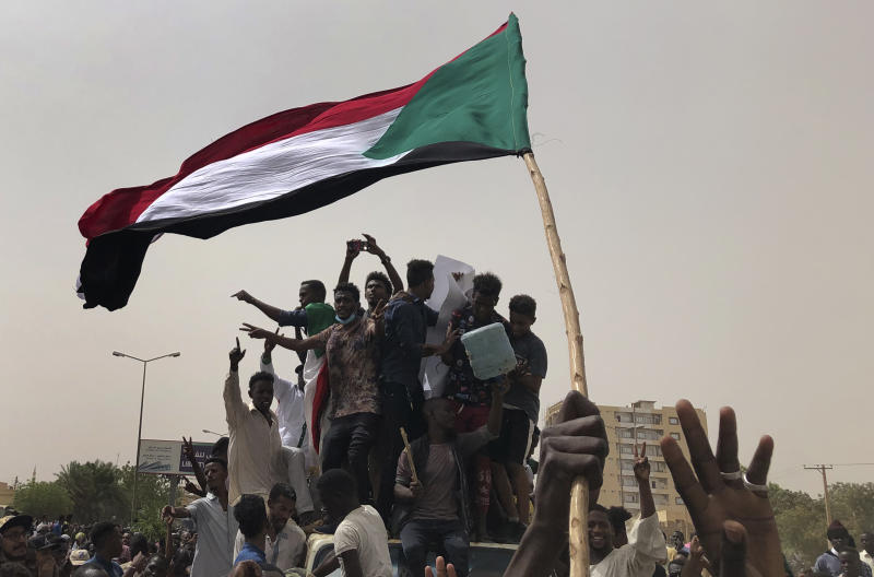 """FILE - In this June 30, 2019, file photo, Sudanese protesters shout slogans as they march during a demonstration against the military council, in Khartoum, Sudan. An African Union envoy says Sudan's ruling military council and the country's pro-democracy movement have reached a power-sharing agreement, including a timetable for a transition to civilian rule. Mohammed el-Hassan Labat said early Friday, July 5, that both sides agreed to form a joint sovereign council that will rule the country for """"three years or a little more."""" The sides agreed to five seats for the military and five for civilians with an additional seat going to a civilian with military background. (AP Photo/Hussein Malla, File)"""