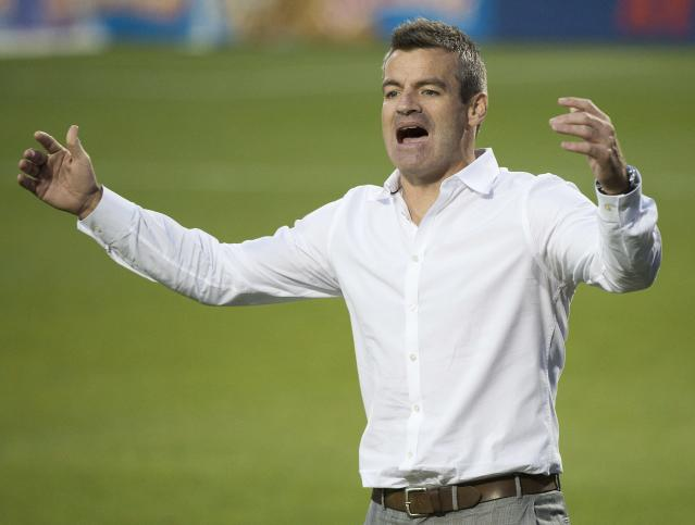 Toronto FC head coach Ryan Nelsen argues a call with one of the officials while playing against Sporting Kansas City during second-half MLS soccer game action in Toronto, Saturday, July 26, 2014. (AP Photo/The Canadian Press, Nathan Denette)
