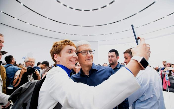 Apple CEO Tim Cook poses for a selfie with journalist Britta Weddeling during a launch event in California in 2018 - AFP/NOAH BERGER
