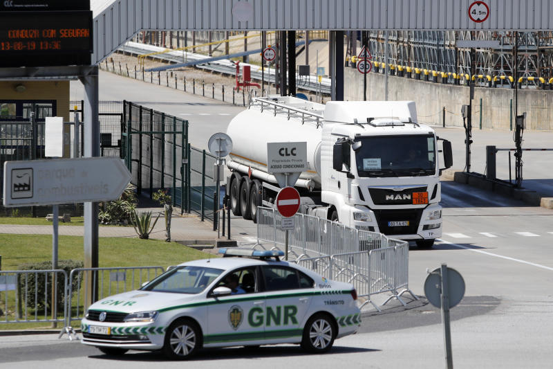 A police car escorts a tanker truck leaving a fuel depot in Aveiras, outside Lisbon, Tuesday, Aug. 13, 2019. Soldiers and police officers are driving tanker trucks to distribute gas in Portugal as an open-ended truckers' strike over pay enters its second day. The government has issued an order allowing the army to be used. (AP Photo/Armando Franca)