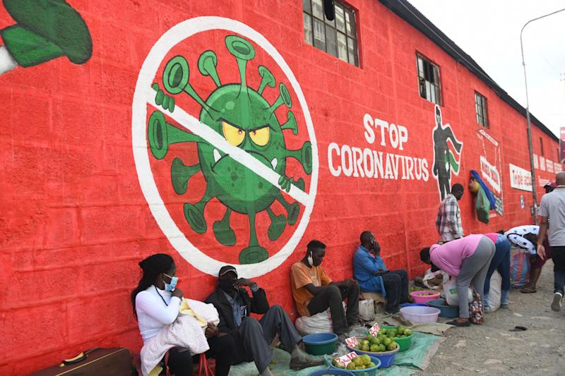 Traders sell their wares below graffiti raising awareness about Covid-19 in Nairobi last month: AFP via Getty Images