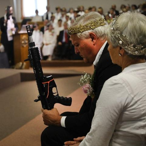 Members carry guns while some wear crowns, often made of bullets - Credit: Spencer Platt/Getty