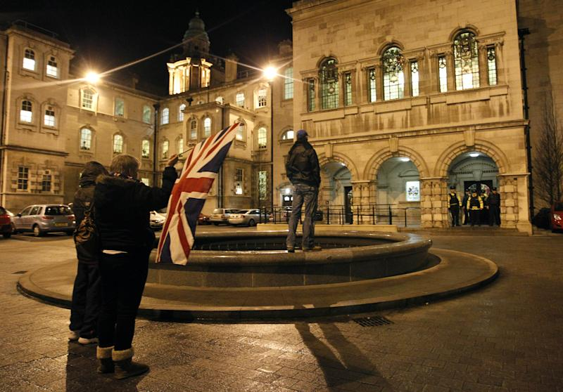 Loyalists hold a British flag inside the grounds of Belfast City Hall, in Northern Ireland, Monday, Dec. 3, 2012. A Protestant mob stormed into the grounds of Belfast City Hall and clashed with police Monday night after the council voted to remove the British flag from the building for most of the year. The Police Service of Northern Ireland said five of their officers and two security guards were injured during the hour-long melee outside city hall. (AP Photo/Peter Morrison)
