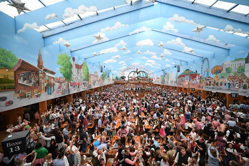 People dressed in traditional clothes sit inside a beer tent after the Oktoberfest parade in Munich, Germany, September 22, 2019. REUTERS/Andreas Gebert