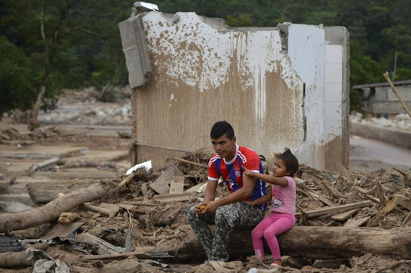 A man and his daughter remain amid rubble in Mocoa, Putumayo department, Colombia on April 4, 2017