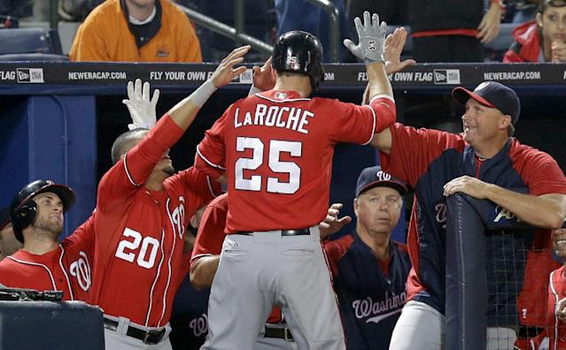 Washington Nationals' Adam LaRoche is high-fived by teammates after hitting a home run in the 15th inning of a baseball game against the Atlanta Braves, Sunday, Aug. 18, 2013, in Atlanta. (AP Photo/David Goldman)