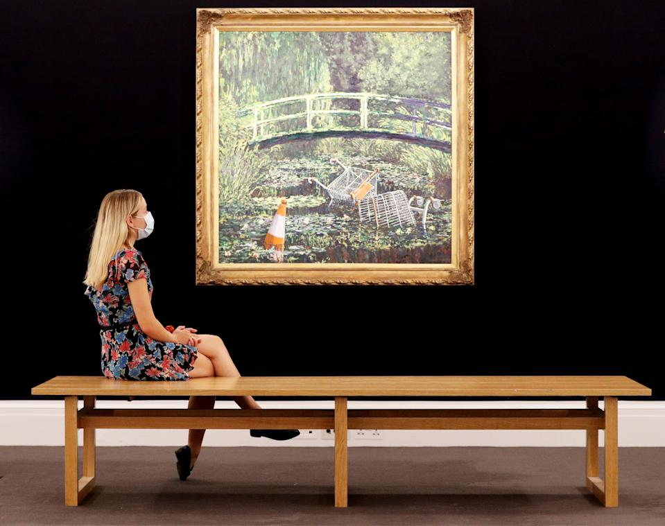 Embargoed to 1330 Friday September 18 A visitor looks at Banksy's 'Show me the Monet' on display at Sotheby's in central London. Banksy's contemporary re-interpretation of Claude Monet's depiction of the Japanese bridge in his garden at Giverny will be part of Sotheby's live-streamed auction on 21st October, 2020.