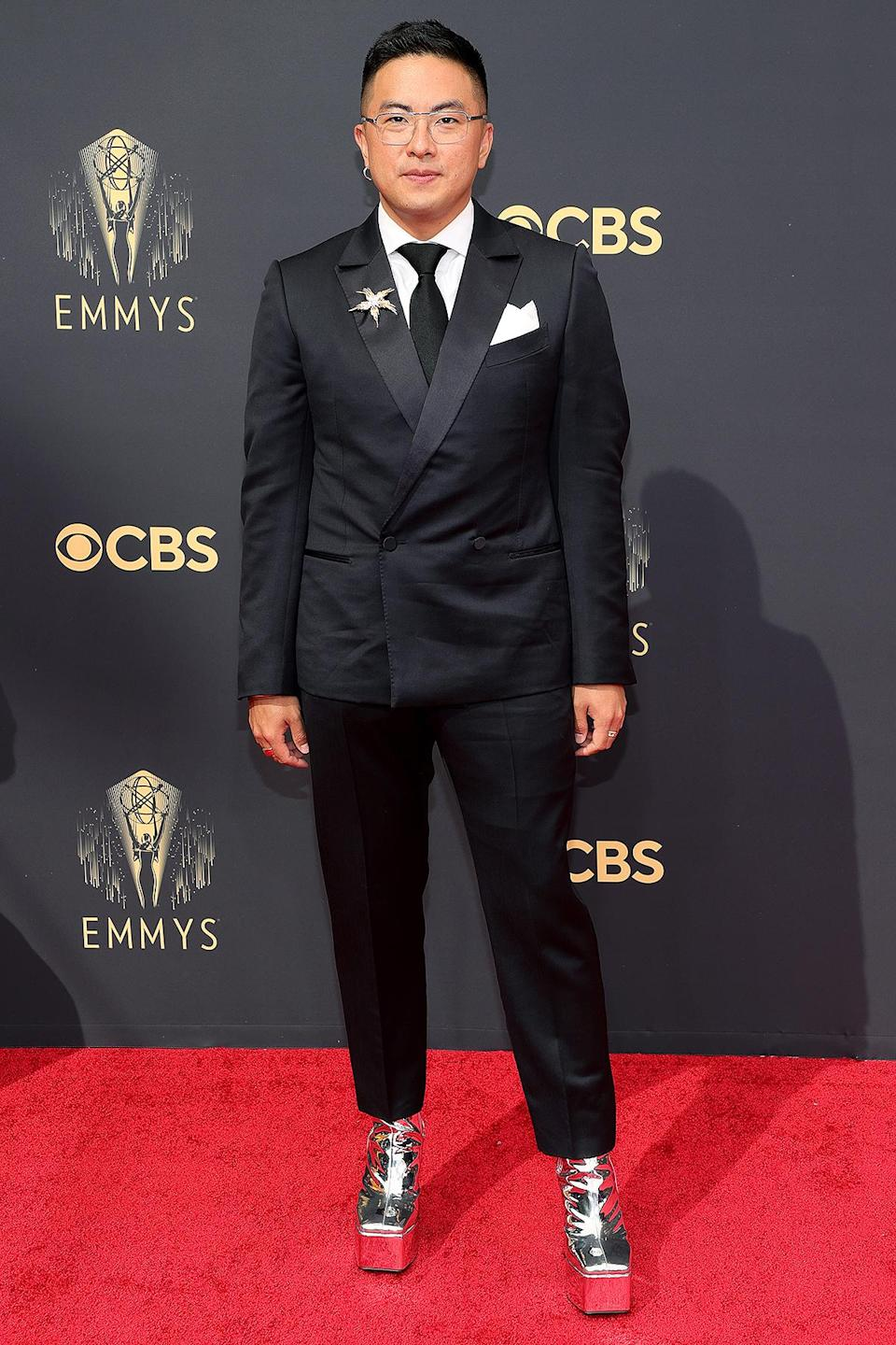 <p>accessorizes his black suit with a star brooch and metallic silver platform shoes.</p>