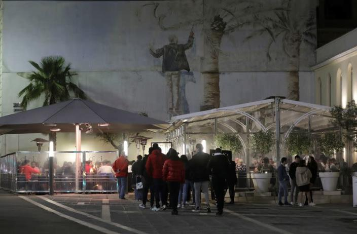 People line in front of a restaurant, as France's Prime Minister announced to close most all non-indispensable locations, notably cafes, restaurants, cinemas, nightclubs and shops from midnight in Nice