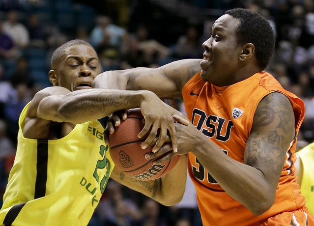 Oregon's Elgin Cook tries to strip Oregon State's Jarmal Reid of the ball in the first half of an NCAA college basketball game in the Pac-12 men's tournament, Wednesday, March 12, 2014, in Las Vegas. (AP Photo/Julie Jacobson)