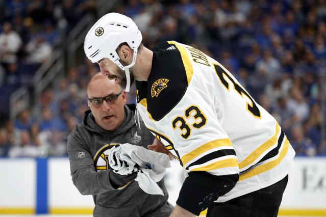 Boston Bruins defenseman Zdeno Chara (33), of Slovakia, is helped off the ice after getting hit in the face with the puck during the second period of Game 4 of the NHL hockey Stanley Cup Final against the St. Louis Blues Monday, June 3, 2019, in St. Louis. (AP Photo/Jeff Roberson)