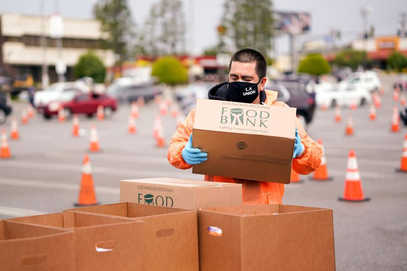 A volunteer with Los Angeles County Federation of Labor, AFL-CIO, hands out boxes of food to LAX workers in the parking lot of The Forum during the outbreak of the coronavirus disease (COVID-19), in Inglewood
