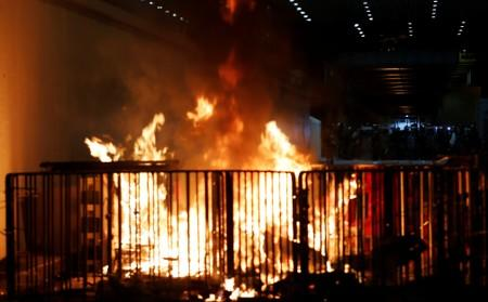 A barricade burns as riot police stand guard, after a march to call for democratic reforms in Hong Kong