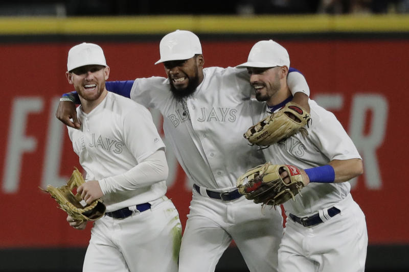 Toronto Blue Jays outfielders Billy McKinney, Teoscar Hernandez and Randal Grichuk, from let, celebrate after the Blue Jays defeated the Seattle Mariners 7-5 in a baseball game Saturday, Aug. 24, 2019, in Seattle. (AP Photo/Ted S. Warren)