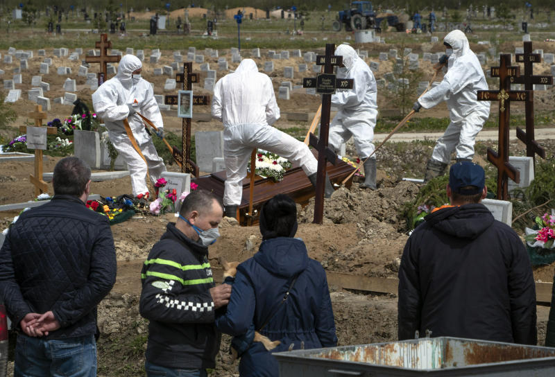 Grave diggers wearing protective suits bury a COVID-19 victim as relatives and friends stand at a safe distance, in the section of a cemetery reserved for coronavirus victims in Kolpino, outside St.Petersburg, Russia, Friday, May 15, 2020. (AP Photo/Dmitri Lovetsky)