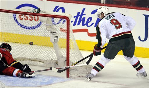 Minnesota Wild's' Mikko Koivu (9), of Finland, puts the puck past Calgary Flames' Mark Giordano for a goal during the first period of their NHL hockey game in Calgary, Alberta, Monday, April 15, 2013. (AP Photo/The Canadian Press, Larry MacDougal)