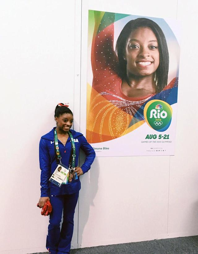 <p>Simone Biles poses in front of her own poster in Rio. (@NBCOlympics/Twitter) </p>