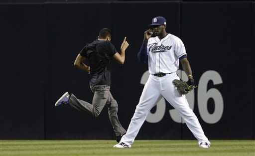 A fan runs past San Diego Padres center fielder Cameron Maybin as he races across the outfield during the seventh inning of their baseball game against the St. Louis Cardinals Tuesday, Sept. 11, 2012, in San Diego. (AP Photo/Gregory Bull)