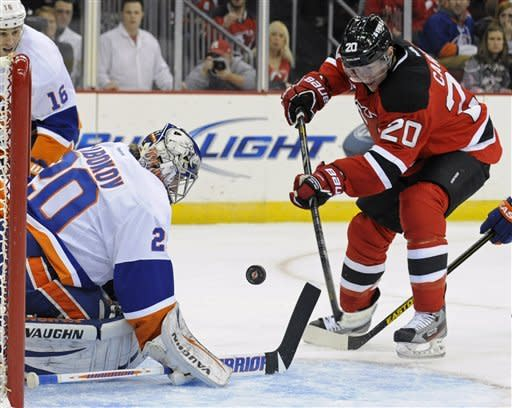 New Jersey Devils' Ryan Carter shoots the puck by New York Islanders goaltender Evgeni Nabokov, left, for a goal during the second period of an NHL hockey game Thursday, Jan. 31, 2013, in Newark, N.J. (AP Photo/Bill Kostroun)