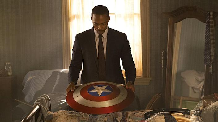 Sam Wilson stands holding the shield of Captain America looking somber in The Falcon and the Winter Soldier