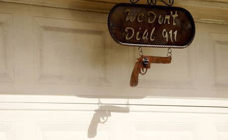 "A sign reading ""We don't dial 911"" hangs outside Fernando Rivera Jr.'s house in Brownsville, Texas September 2, 2014. REUTERS/Rick Wilking"