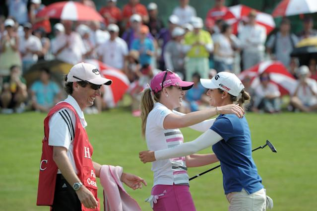 Paula Creamer of the U.S.A., center, and Azahara Munoz of Spain, right, embrace each other as Creamer's caddie Colin Cann, left, smiles after Creamer won the HSBC Women's Champions golf tournament in Singapore on Sunday, Mar. 2, 2014. (AP Photo/Joseph Nair)