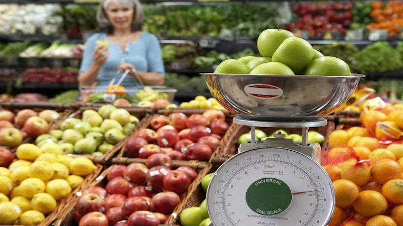 Mature woman in supermarket, focus on weighing scale