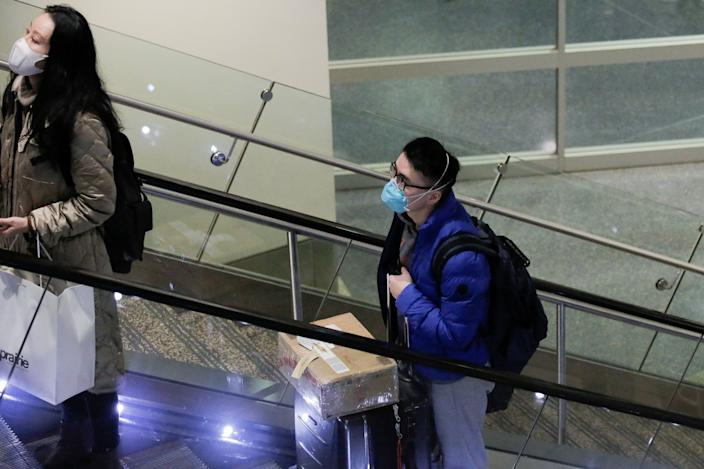 Travellers wearing masks arrive on a direct flight from China, after a spokesman from the U.S. Centers for Disease Control and Prevention (CDC) said a traveller from China had been the first person in the United States to be diagnosed with the Wuhan coronavirus, at Seattle-Tacoma International Airport in SeaTac, Washington, U.S. January 23, 2020.  REUTERS/David Ryder