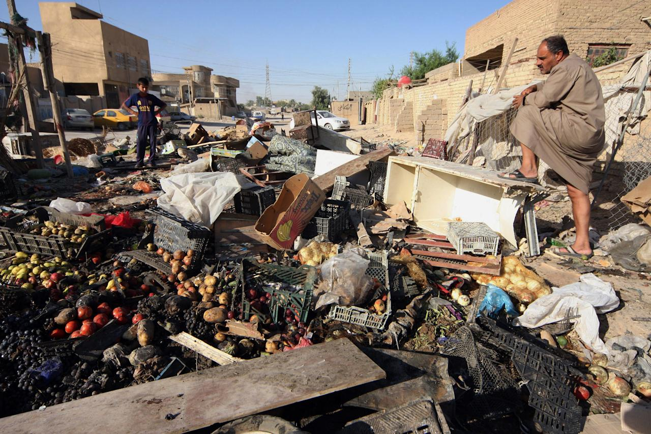 People inspect the aftermath of a car bomb attack in Karbala, 50 miles (80 kilometers) south of Baghdad, Iraq, Sunday, Aug. 11, 2013. A wave of car bombings targeting those celebrating the end of Ramadan across Iraq killed scores of people Saturday, a bloody reminder of the inability of Iraqi authorities to stop violence threatening to spiral out of control. (AP Photo)