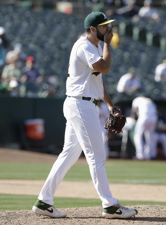 Oakland Athletics' pitcher Lou Trivino reacts on the mound after the Los Angeles Angels scored a run during the 11th inning of a baseball game in Oakland, Calif., Wednesday, May 29, 2019. (AP Photo/Jeff Chiu)