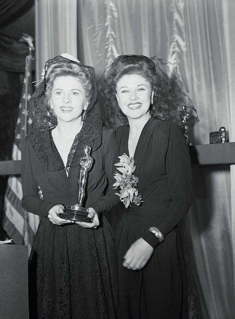 <p>Ginger (right) wore a black long-sleeve dress floral details and a lace hairpiece at the '42 ceremony. She won the Oscar for her role in <em>Roxie Hart</em> the year before, and pictured here, she presented the award to Joan Fontaine. </p>