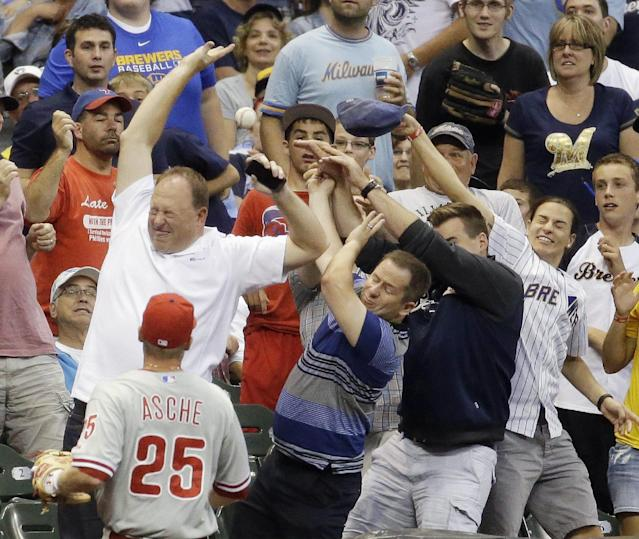 Philadelphia Phillies' Cody Asche watches as fans go after a foul ball off the bat of Milwaukee Brewers' Logan Schafer during the fourth inning of a baseball game Tuesday, July 8, 2014, in Milwaukee. (AP Photo/Morry Gash)