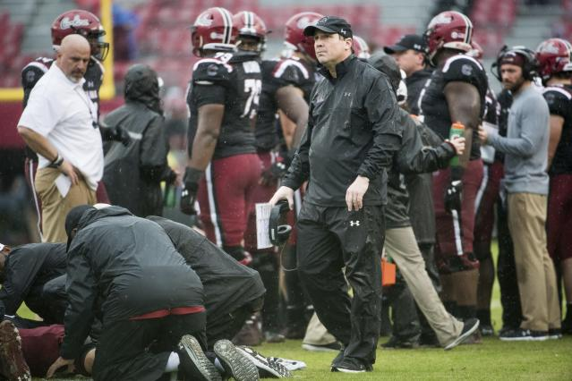 South Carolina head coach Will Muschamp visits an injured player on the field during the second half of an NCAA college football game against Akron Saturday, Dec. 1, 2018, in Columbia, S.C. South Carolina defeated Akron 28-3. (AP Photo/Sean Rayford)