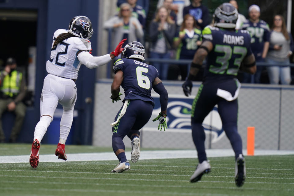 Tennessee Titans running back Derrick Henry (22) fends off Seattle Seahawks strong safety Quandre Diggs (6) as he runs for a touchdown during the second half of an NFL football game, Sunday, Sept. 19, 2021, in Seattle. (AP Photo/Elaine Thompson)