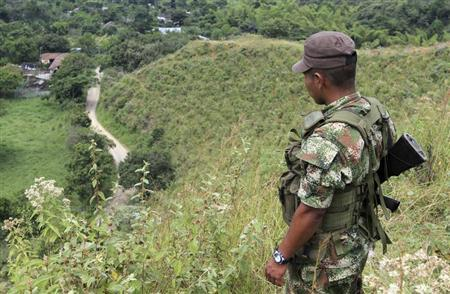 A FARC rebel monitors the delivery of released hostages from a cocoa plantation in Monte Alegre province, in the department of Valle del Cauca