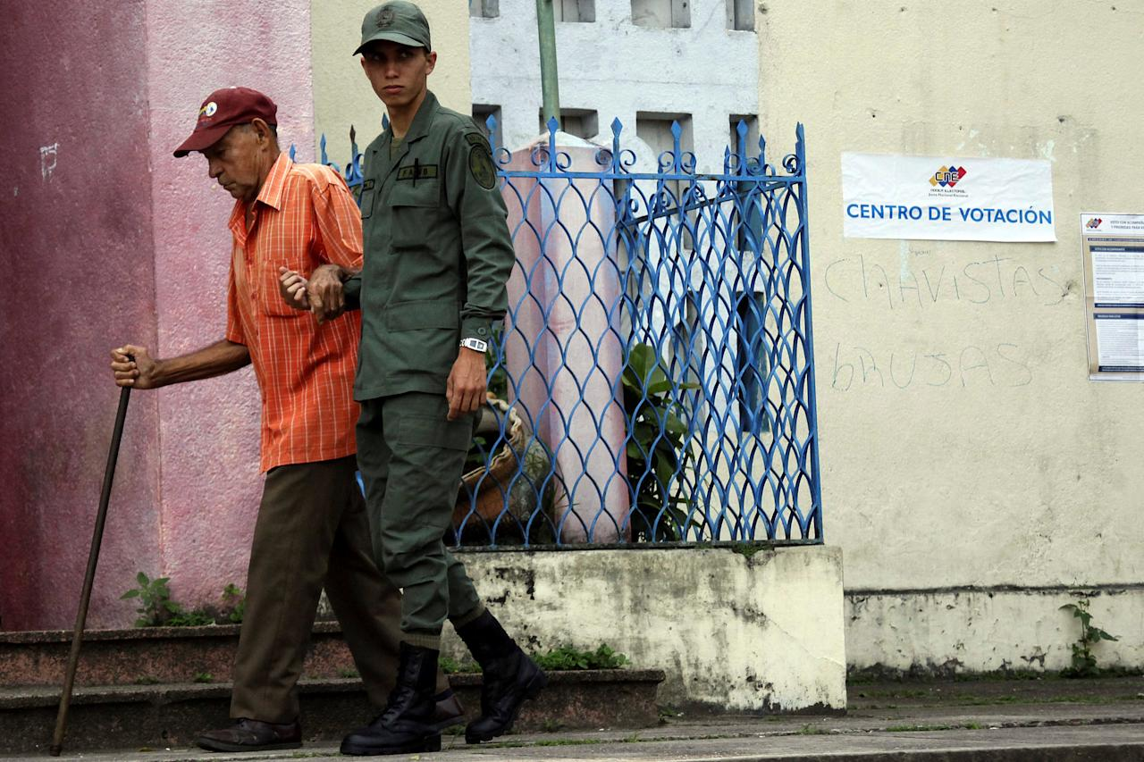 A soldier helps a man outside a polling station during a nationwide election for new mayors, in Rubio, Venezuela December 10, 2017. REUTERS/Carlos Eduardo Ramirez