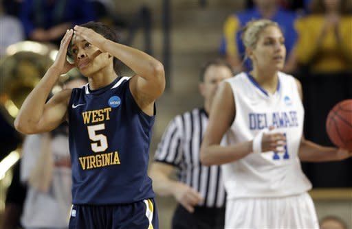 West Virginia forward Averee Fields, left, reacts after fouling Delaware guard/forward Elena Delle Donne, right, during the second half of a first-round game in the women's NCAA college basketball tournament in Newark, Del., Sunday, March 24, 2013. Fields fouled out of the game on the play. Delaware won 66-53. (AP Photo/Patrick Semansky)