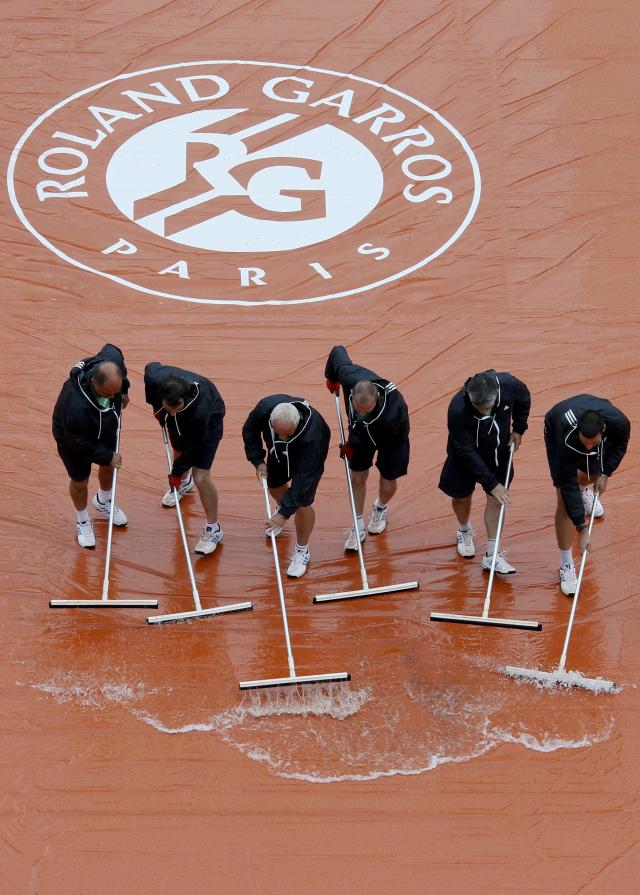 Workers sweep water off a tarp as rain interrupts a men's singles match between Novak Djokovic of Serbia and Joao Sousa of Portugal at the French Open tennis tournament at the Roland Garros stadium in Paris May 26, 2014. REUTERS/Gonzalo Fuentes (FRANCE - Tags: SPORT TENNIS)