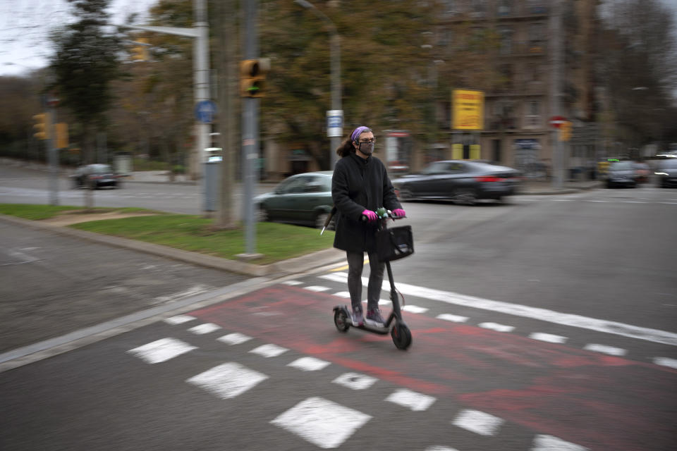 "Victoria Martinez, 44, rides her electric scooter on her way home in Barcelona, Spain, Wednesday, Feb. 10, 2021. By May this year, barring any surprises, Martinez will complete a change of both gender and identity at a civil registry in Barcelona, finally closing a patience-wearing chapter that has been stretched during the pandemic. The process, in her own words, has also been ""humiliating."" (AP Photo/Emilio Morenatti)"