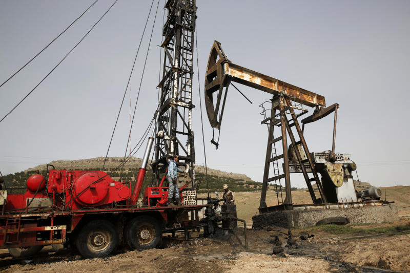 FILE - This March 27, 2018 file photo shows Syrian workers fixing pipes of an oil well at an oil field controlled by a U.S-backed Kurdish group, in Rmeilan, Hassakeh province, Syria. President Donald Trump's decision to dispatch new U.S. forces to eastern Syria to secure oil fields is being criticized by some experts as ill-defined and ambiguous. But the residents of the area, one of the country's most remote and richest regions, hope the U.S. focus on eastern Syria would bring an economic boon and eliminate what remains of the Islamic State group. (AP Photo/Hussein Malla, File)