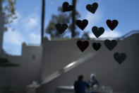 A cafeteria window is decorated with heart-shaped cutouts as hospital staff members eat their lunch in a recently reopened dining area at Mission Hospital in Mission Viejo, Calif., Friday, Feb. 19, 2021. California's virus cases, infection rates, and hospitalizations have dropped precipitously after reaching record highs in early January. (AP Photo/Jae C. Hong)
