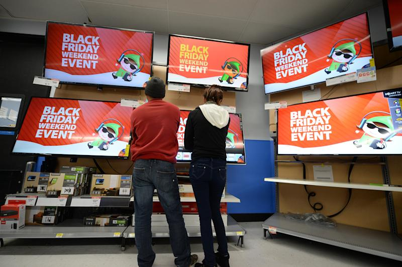 Shoppers consider televisions for sale at the Walmart in the Crenshaw district of Los Angeles on Black Friday, November 29, 2013. AFP PHOTO / Robyn Beck (Photo credit should read ROBYN BECK/AFP/Getty Images)