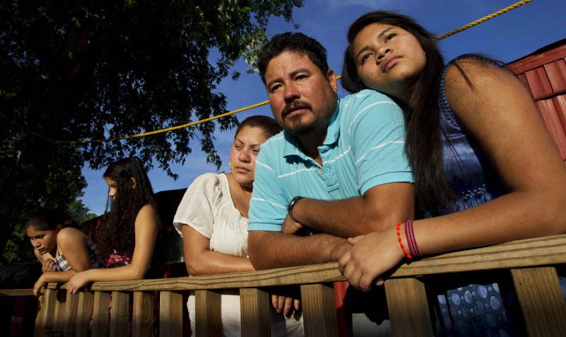 "In this Thursday, April 13, 2012 photo, Diane Martell, 17, right, leans on her parents Maurcio and Guadalupe on the porch of their home in Bessemer, Ala. The Martells are illegal immigrants, as are most of the residents of this trailer park, and they live in fear of Alabama's harsh immigration laws. From left are her sisters Monserrat, 11, and Alexa, 12. Diane says she is tired of watching the fear in her father's face every time he drives, tired of her mother begging her not to walk to school on the days the ICE van is parked down the street, tired of being told that she cannot get a driver's license, or a job or maybe even a college education because she doesn't have a Social Security number. ""We are human beings,"" Martell says. ""We are not criminals, and we are not aliens and we cannot just stay silent."" (AP Photo/Dave Martin)"