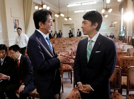 Japan's Prime Minister Shinzo Abe (L) talks with Shinjiro Koizumi at the party lawmakers' meeting after the dissolution of the lower house was announced at the Parliament in Tokyo