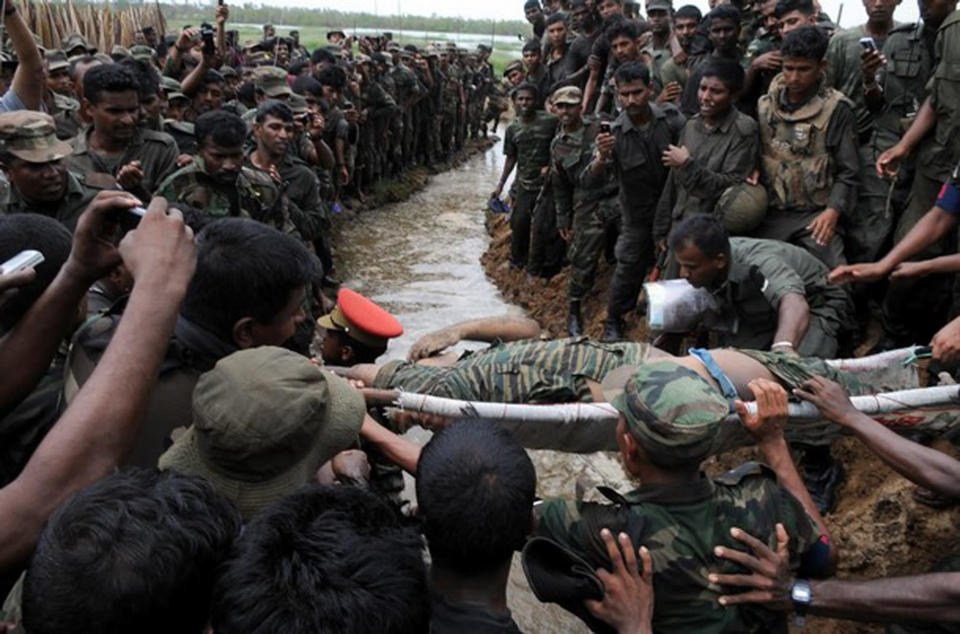 FILE- In this May 19, 2009 file photo, Sri Lankan soldiers gather as the body of Tamil rebel leader Velupillai Prabhakaran is carried on a stretcher in Mullaittivu, Sri Lanka. Tamil rebels fought a nearly three-decade separatist war accusing Sinhalese-controlled governments of systemic marginalization since independence from the British in 1948. Sri Lankan forces in 2009 crushed the rebels to end a war that claimed at least 100,000 lives according to the U.N. (AP Photo, File)
